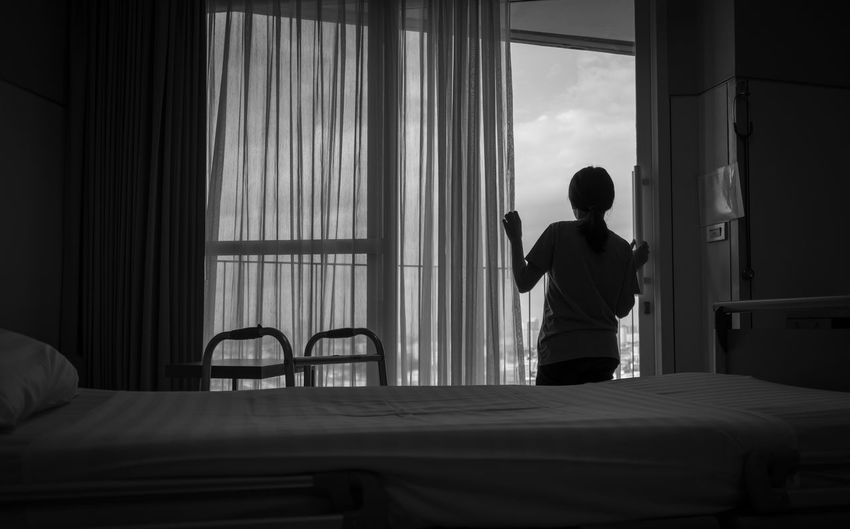 Rear view of woman looking through window at hospital