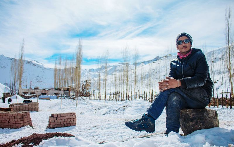 Young man sitting on snow covered mountains