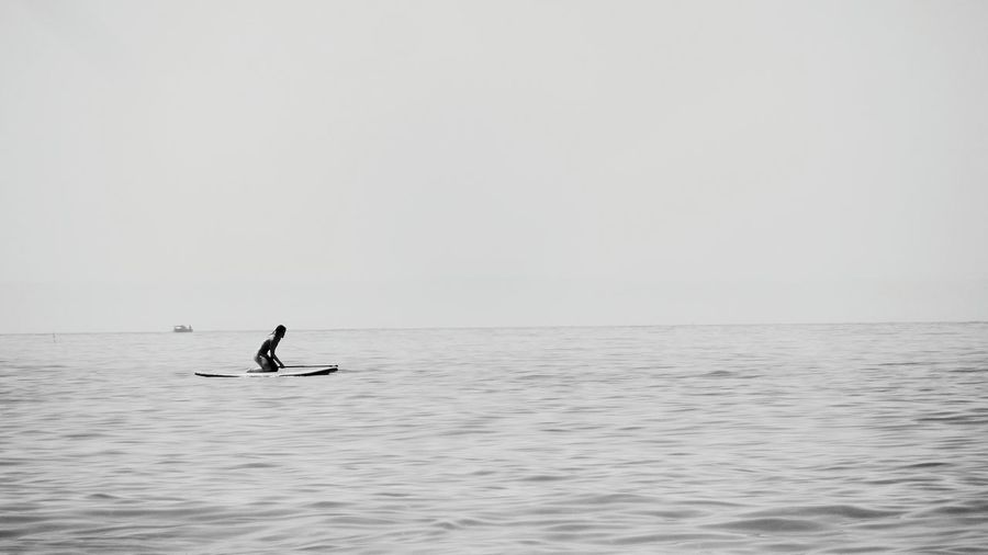 Man paddleboarding on sea against clear sky