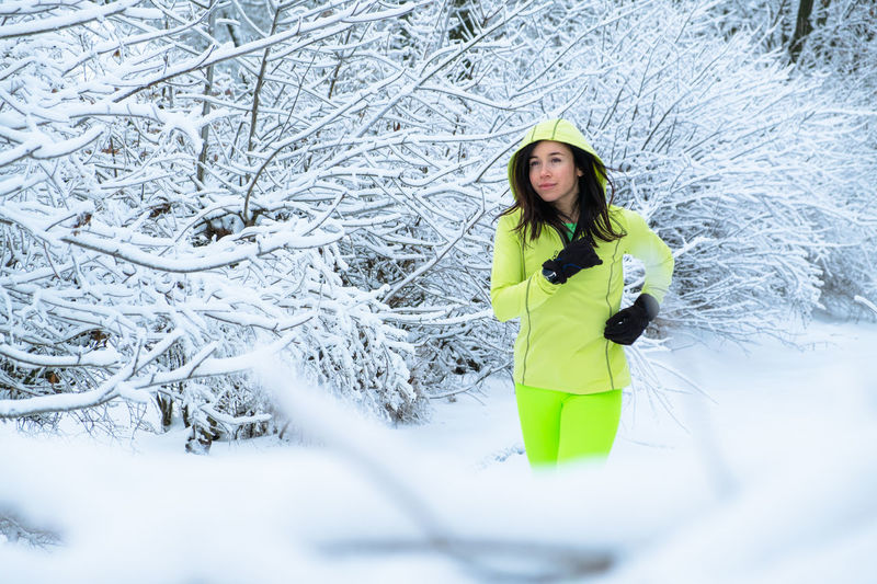 Portrait of woman standing on snow covered land