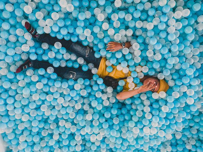 High angle view of man lying admist balloons