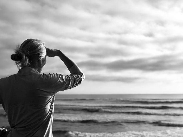 Woman looking towards sea while standing at beach against sky