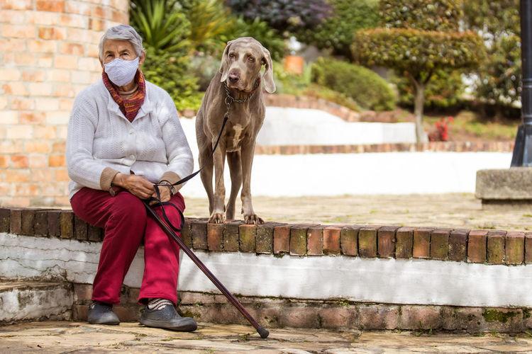 Full length portrait of man holding dog sitting outdoors