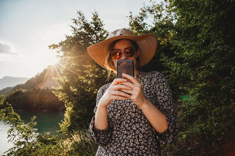 Woman with hat and sunglasses using mobile phone in sunset on the lake side
