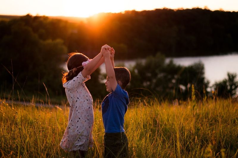 Children standing on field against sky during sunset