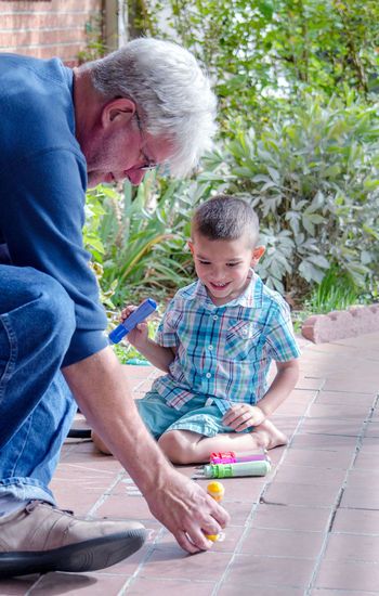 Grandson Playing With Crayons By Grandfather