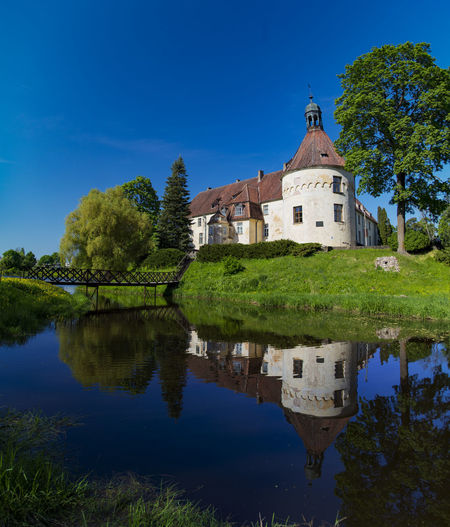 Reflected Jaunpils Latvia Architecture Blue Building Building Exterior Built Structure Day Green Color House Lake Nature No People Outdoors Place Of Worship Plant Reflection Religion Sky Tree Water Waterfront