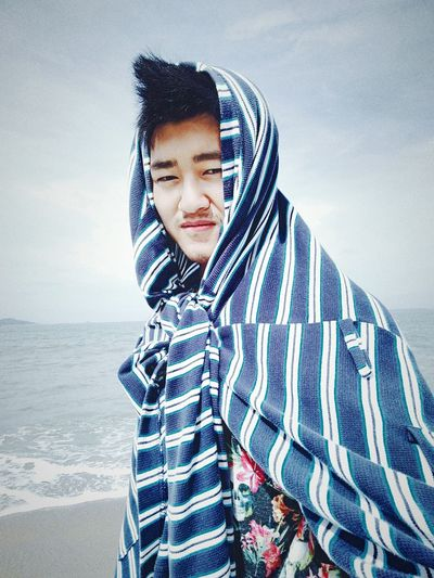 Portrait Of Young Man Wrapped In Towel At Beach