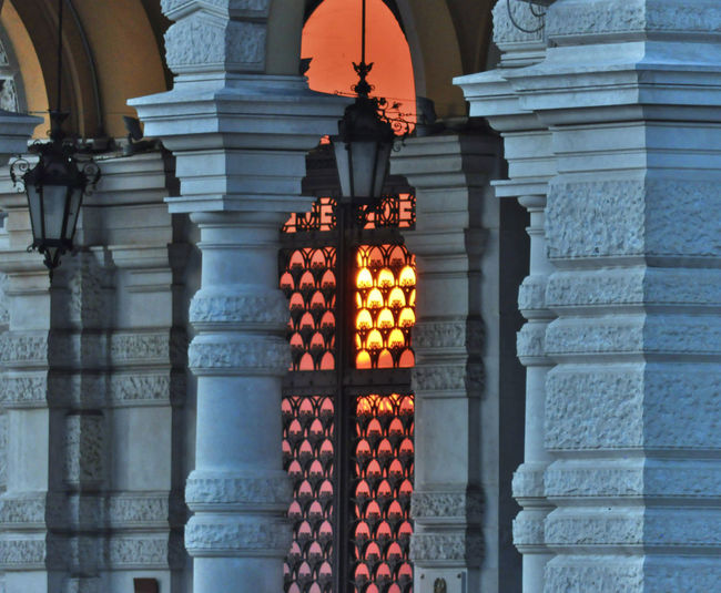 Trieste Arch Architectural Feature Availablelight Building Built Structure Cities At Night City Column Discover Light Lamp Nikon No People Orange Color Ornament Red Stone Wall Structures & Lines Sun Reflection Taking Photos The Architect – 2016 EyeEm Awards Trieste Twilight