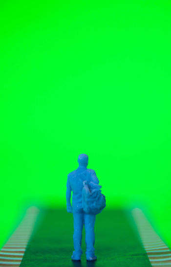 Rear view of man sitting against green wall