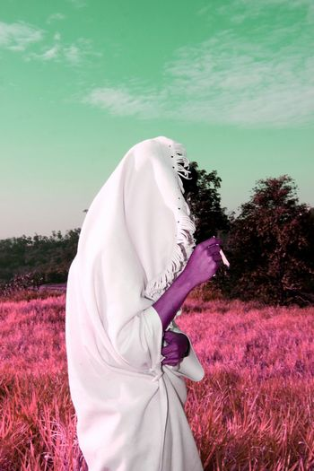 Man With Covered Blanket Smoking Cigarette On Grassy Field Against Sky