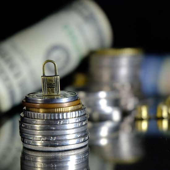 Close-Up Of Padlock On Stacked Coins