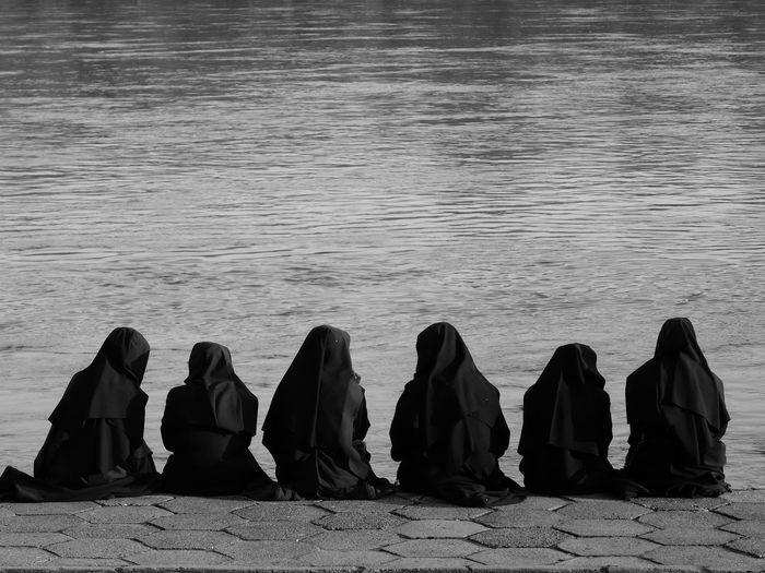 Rear view of women hijab praying at lakeshore