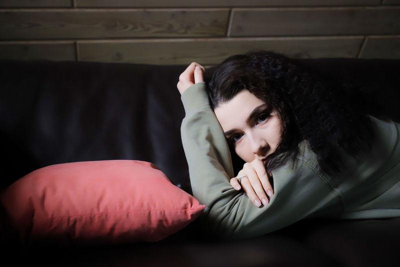 Portrait of woman lying down on sofa