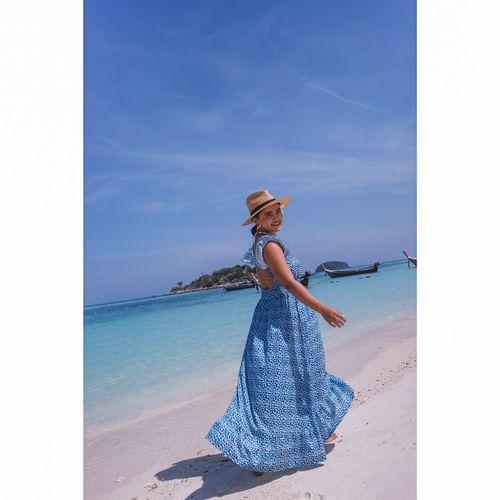 Full length portrait of woman wearing hat on beach against sky