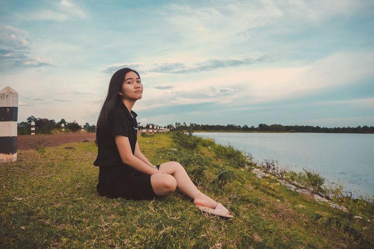 Portrait of woman sitting by lake