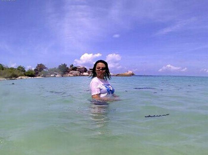 Full length portrait of smiling girl swimming in sea