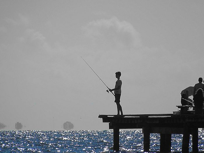 Man fishing on water against clear sky