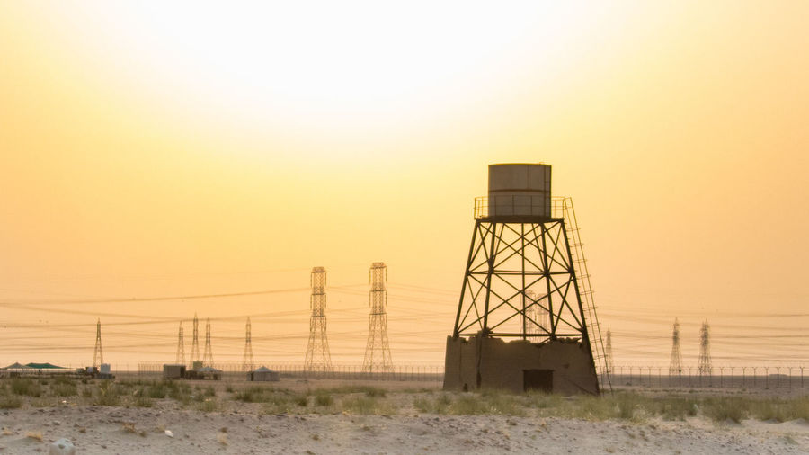 Water tower on landscape against sky during sunset