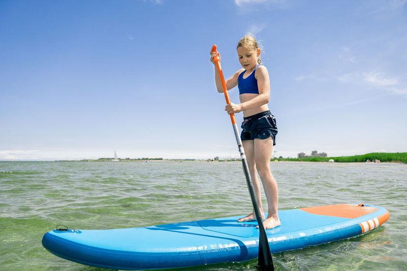 Full length of boy standing on sea against blue sky