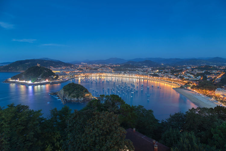 High angle view of illuminated city by river against blue sky