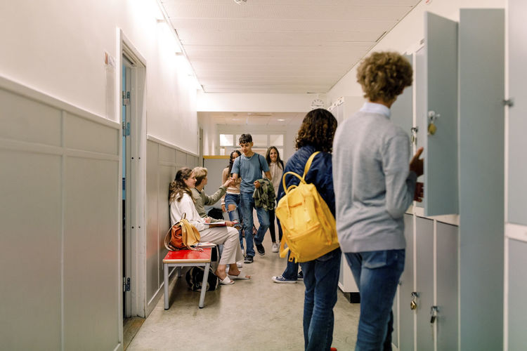 Rear view of people walking in corridor