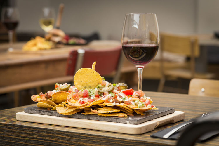 Nachos by red wine in glass served on wooden table
