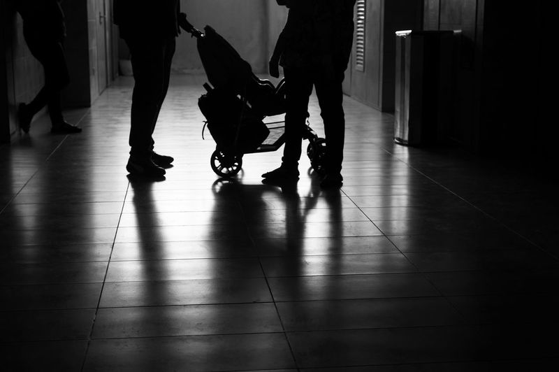 Low Section Of Silhouette People With Baby Stroller In Corridor