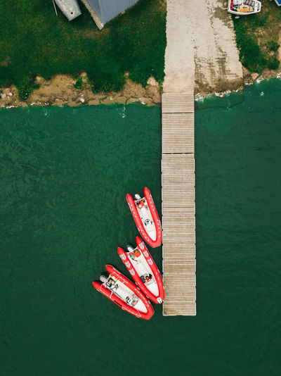 Red inflatable boats stand near the pier.aerial view by drone.