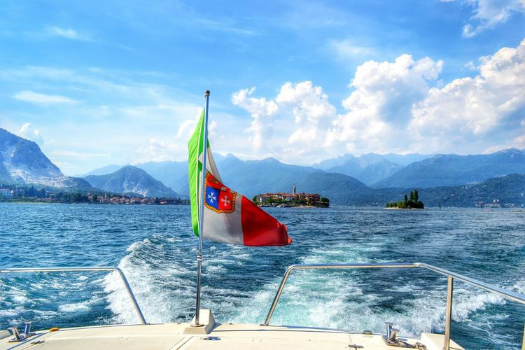 Boats in sea with mountain range in background