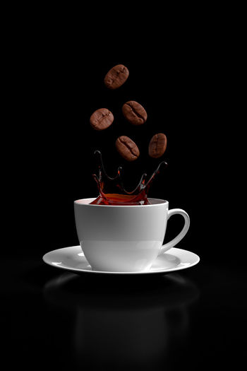 Close-up of coffee cup against black background