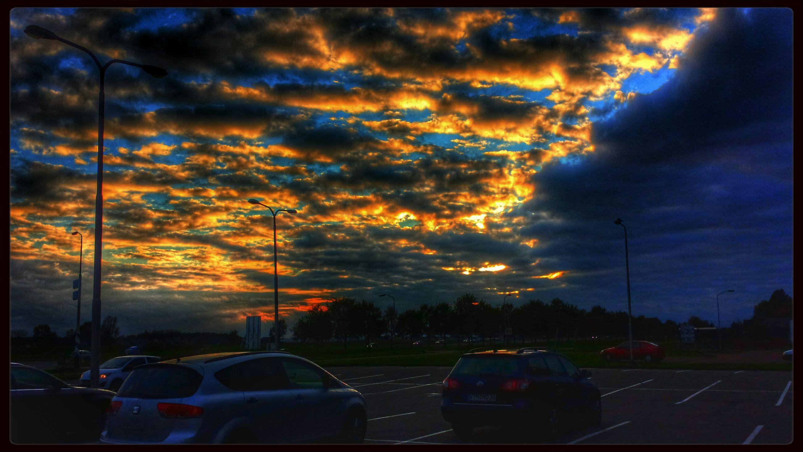 transportation, sky, car, cloud - sky, land vehicle, mode of transport, sunset, cloudy, transfer print, road, auto post production filter, weather, cloud, overcast, dramatic sky, street light, street, storm cloud, dusk, atmospheric mood