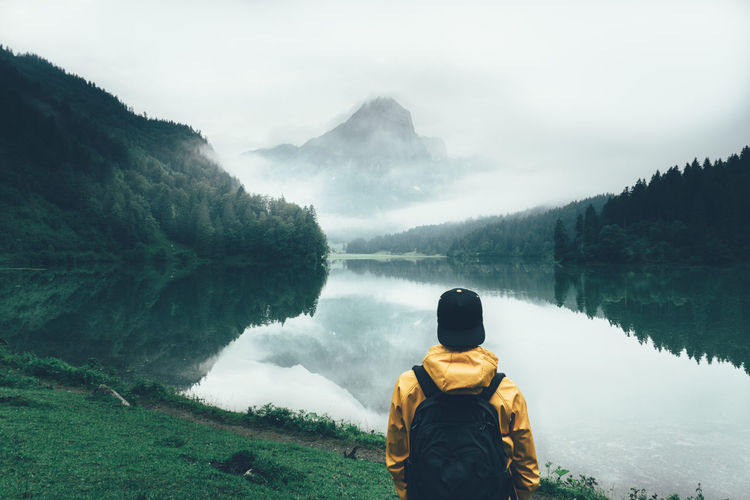 Rear view of man looking at obersee lake by mountains in foggy weather