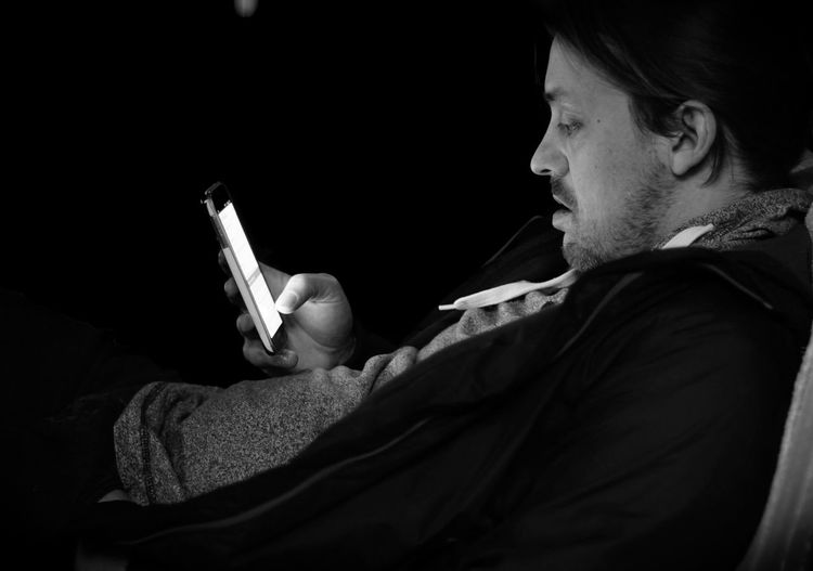 Side View Of Man Using Phone In Darkroom