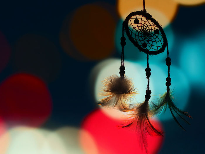 Close-Up Of Dreamcatcher Hanging Against Lens Flares