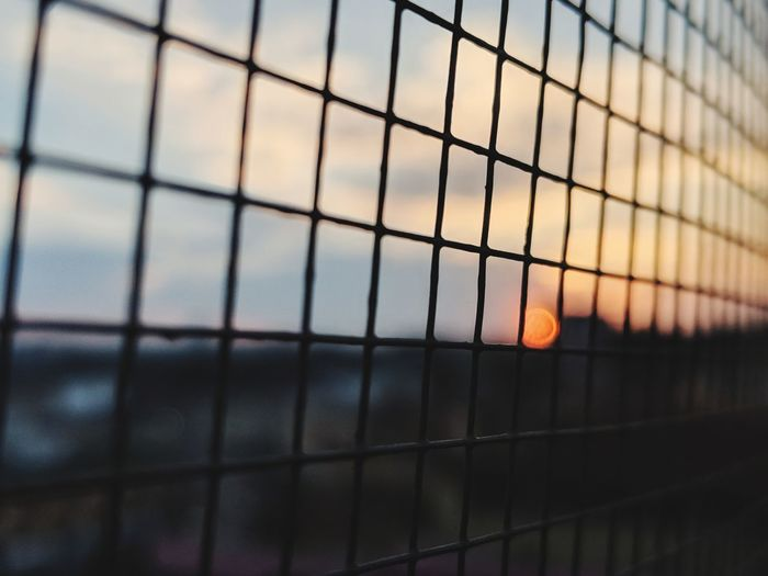 Full frame shot of metal fence against sky during sunset