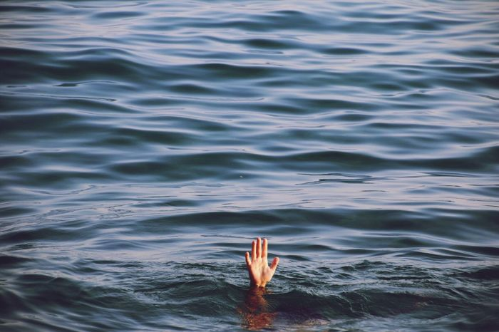 Cropped hand emerging from sea