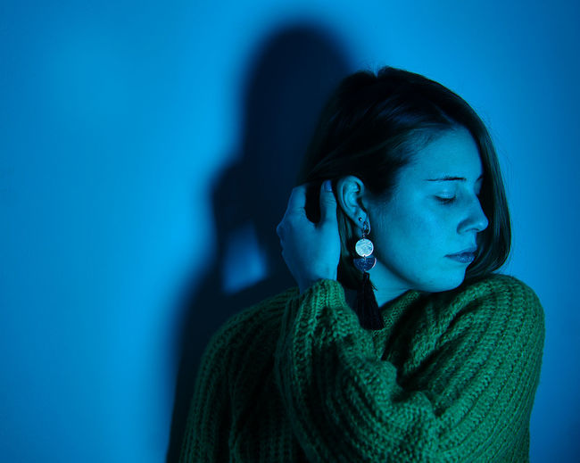 Portrait of young woman looking away against blue wall