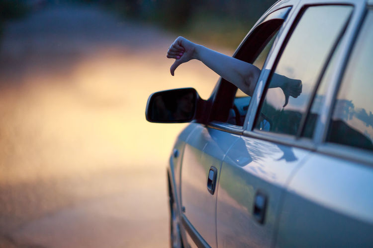 Cropped hand showing thumbs down from car on road