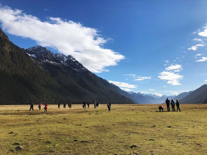 Group of people on field against mountain range
