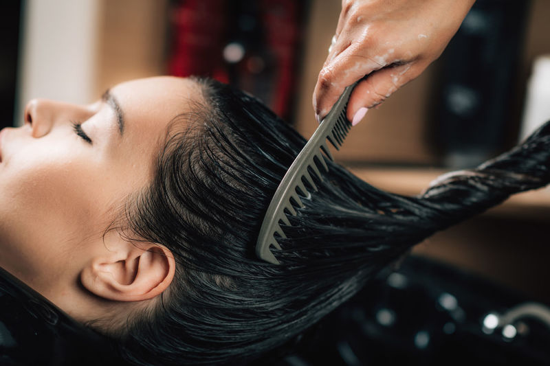 Cropped hand of hairdresser combing woman hair in salon