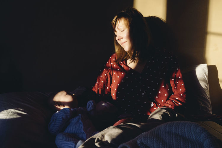 Woman Sitting With Baby On Bed At Home