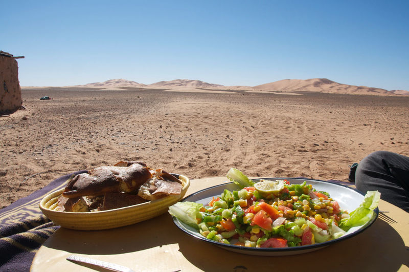 High angle view of salad and bread served in plates at desert