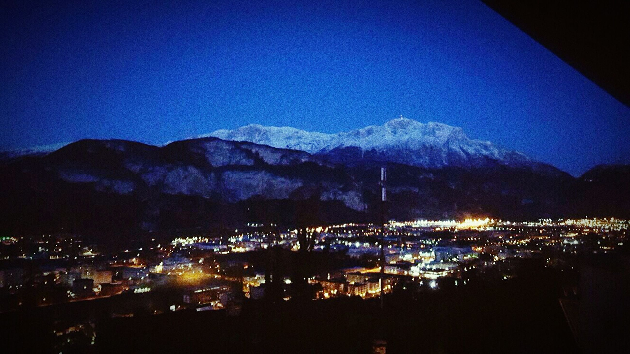 night, illuminated, blue, mountain, sky, reflection, dusk, mountain range, no people, silhouette, nature, built structure, architecture, outdoors, scenics, beauty in nature, city, building exterior, tranquility, luminosity, water, cityscape