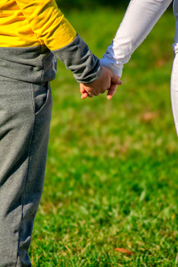Midsection of couple holding hands on field