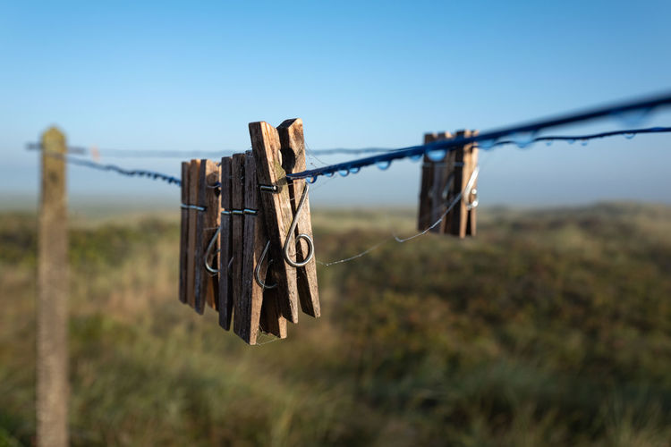 Close-up of clothes peg hanging on rope against fence