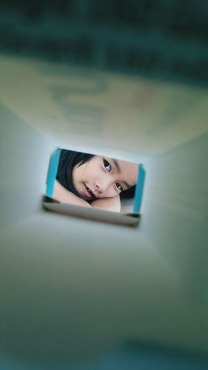 Portrait of cute girl seen through cardboard