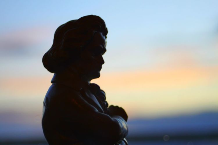 Close-up of silhouette man against sea during sunset