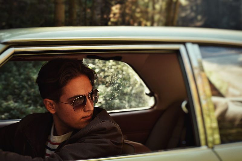 Man wearing sunglasses looking away while sitting in car