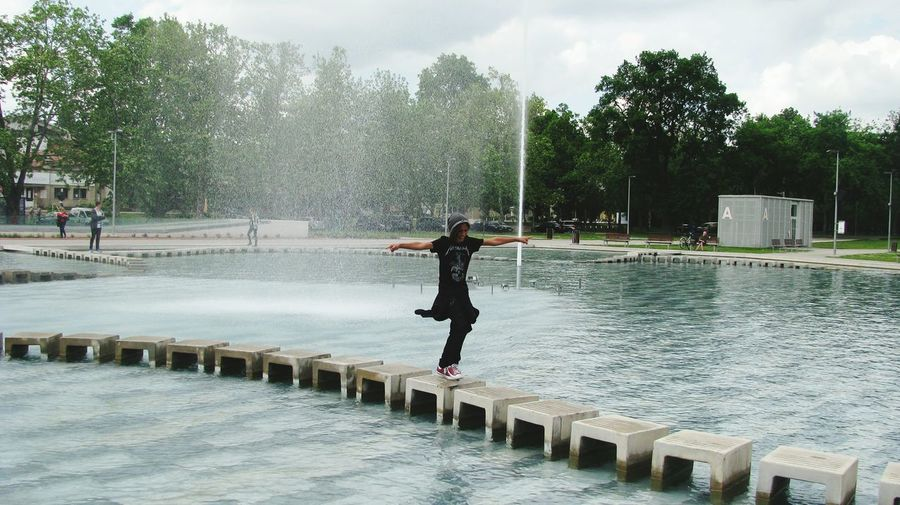 Woman with arms outstretched walking on stepping stones in fountain at park